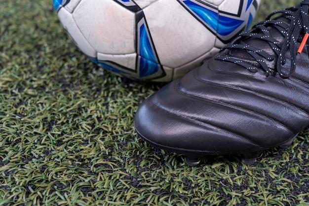 Sapatos de futebol com bola de futebol no campo de grama artificial