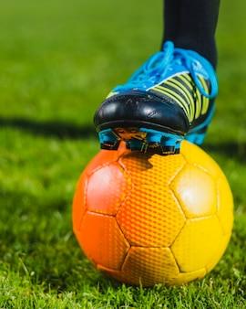 Sapatos de futebol e bola