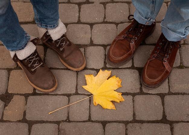 Sapatos de gente em volta de folha amarela