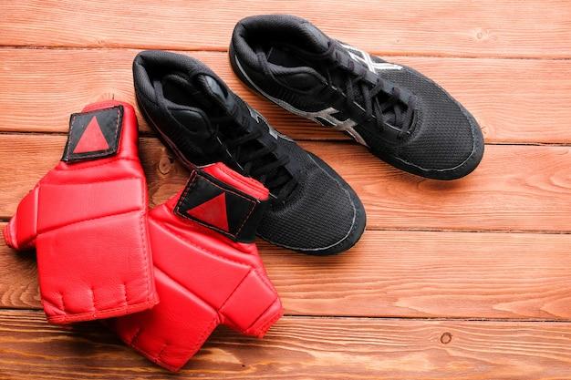 Sapatos de luta livre e luvas de mma no chão de madeira.