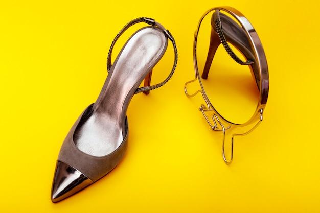 Sapatos de mulher de couro cinza isolados em amarelo