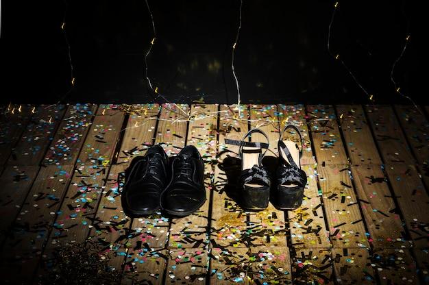 Sapatos de mulher e botas do homem entre confetes