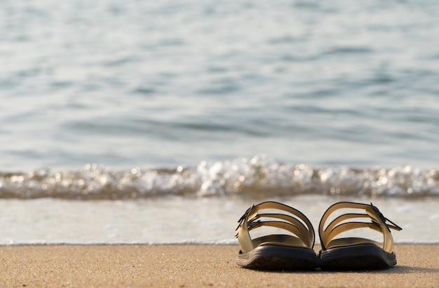 Sapatos de mulher na praia do mar durante o verão.