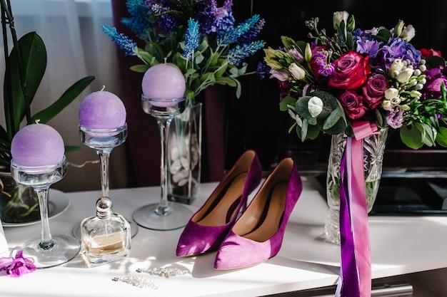 Sapatos de mulheres elegantes violetas, brincos, buquê de flores, velas e perfumes na mesa de pé na mesa de fundo de madeira. noiva de acessório de casamento.