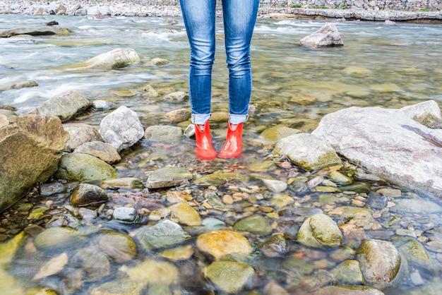 Sapatos de mulheres vermelhas na água nas montanhas dos cárpatos