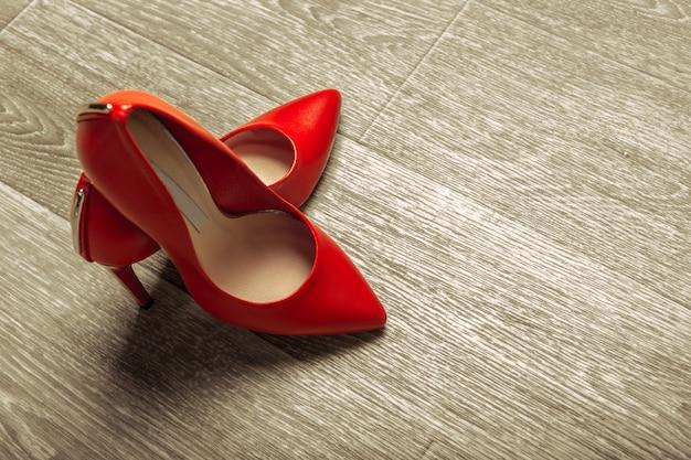 Sapatos de mulheres vermelhas na madeira