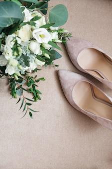 Sapatos de noiva bonitos estão de pé ao lado de um buquê de flores