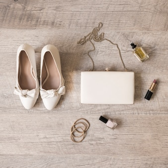 Sapatos de noiva brancos; perfume; batom; hairbands; embreagem e bandas de cabelo em fundo de madeira