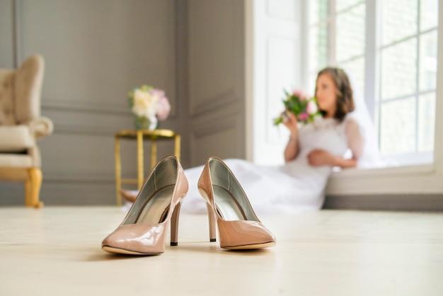 Sapatos de noiva casamento bege no chão com a noiva