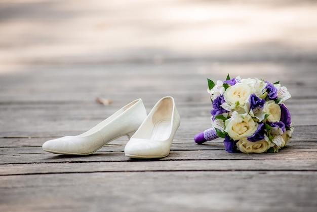 Sapatos de noiva e buquê de noiva deitado na ponte de madeira. sapatos da moda noiva linda em pé no chão de madeira. buquê de noiva deitado sobre as tábuas de madeira.