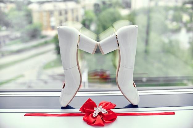 Sapatos de noiva e liga na janela de noiva
