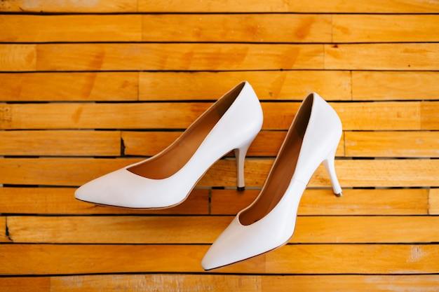 Sapatos de noiva em uma textura de madeira.