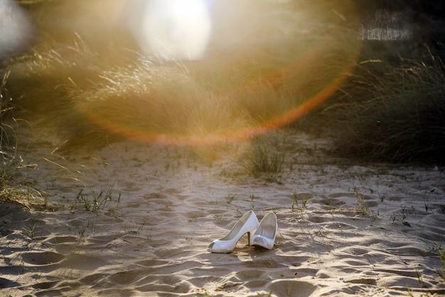 Sapatos de noiva na areia abandonada iluminado com reflexos do sol