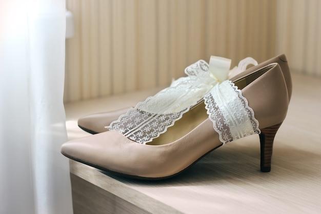 Sapatos de noiva na mesa ao lado da janela
