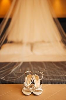 Sapatos de noiva prateados na cama antes da cerimônia