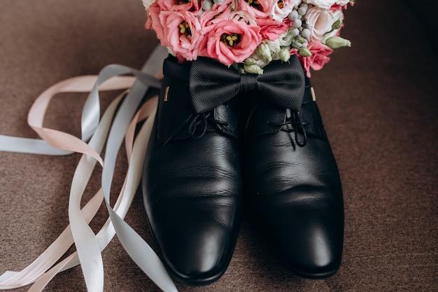 Sapatos de noivo com flores e laço