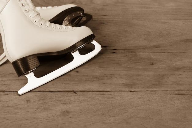 Sapatos de patinação no gelo figura estilo feminino ou mulheres em fundo de madeira