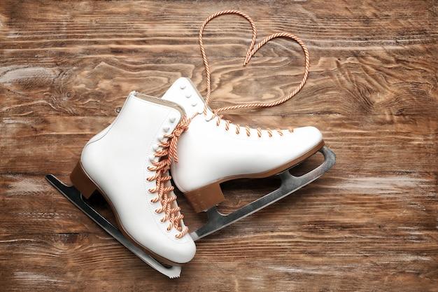 Sapatos de patinar no gelo em fundo de madeira