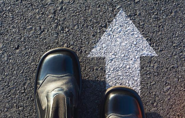 Sapatos de pé na encruzilhada e decidir qual caminho seguir. maneiras de escolher o conceito.
