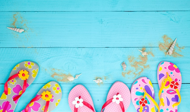 Sapatos de praia com conchas e areia no fundo de madeira, conceito de férias de verão