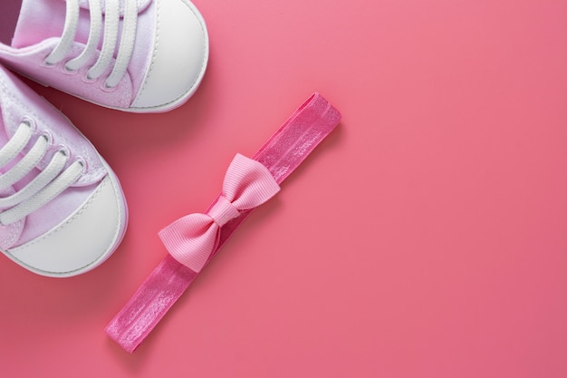 Sapatos de recém-nascidos e faixa de cabeça com laço. garota criativa bebê plana leigos. copie o espaço.
