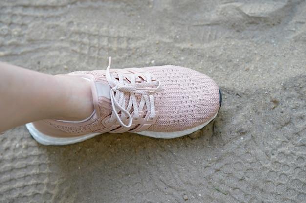 Sapatos de runnung rosa carimbo de um lado na areia com impressões de sapatos