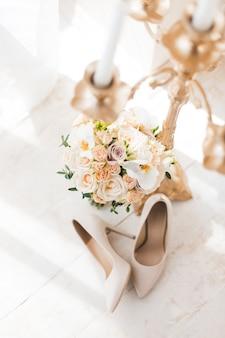 Sapatos de salto alto bege com buquê de casamento e castiçal ao sol da manhã