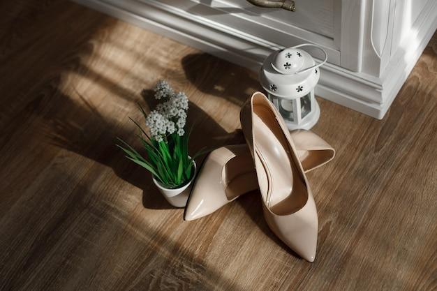 Sapatos de salto alto bege isolados no fundo de madeira com espaço de cópia de texto