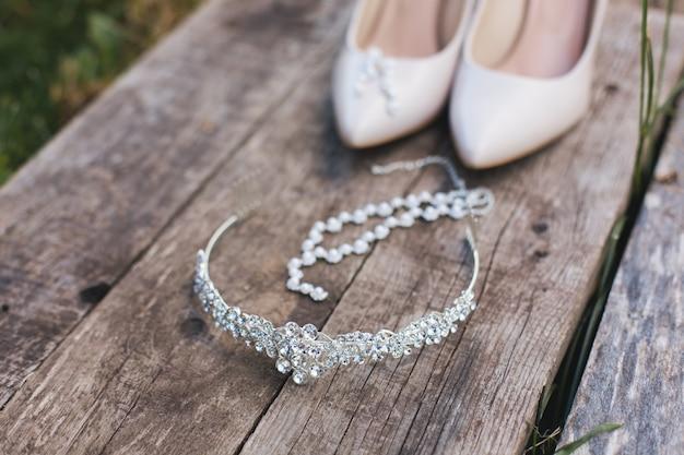Sapatos de salto alto bege, sapatos e jóias de casamento estão sobre uma mesa de madeira vintage