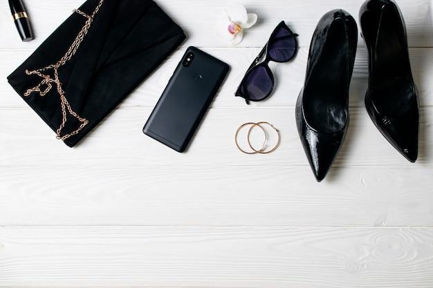 Sapatos de salto alto, bolsa, celular, óculos de sol, batom e brincos