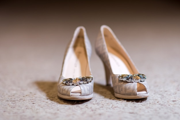 Sapatos de salto alto da noiva na superfície clara.