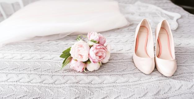 Sapatos de salto alto da noiva. vestido de noiva deslumbrante branco incrível e sapatos de salto alto deitado na cama perto do buquê de casamento rosa no quarto