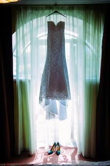Sapatos de salto alto femininos e vestido longo branco da noiva no quarto de hotel.