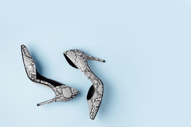 Sapatos de salto alto femininos elegantes sobre fundo azul. camada plana, vista superior.