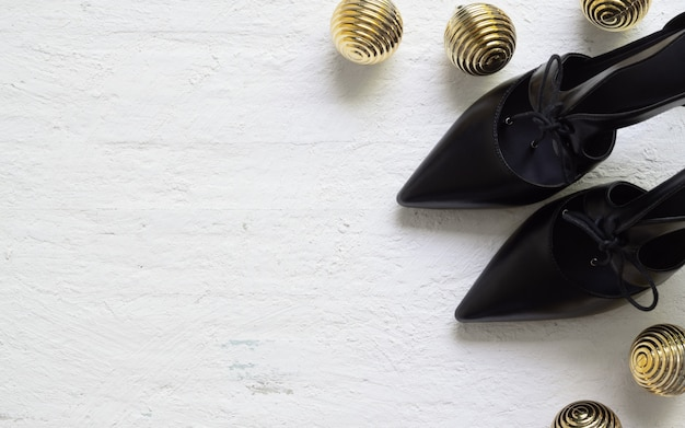 Sapatos de salto alto preto liso leigos e bola de natal dourada