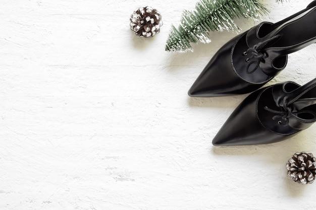 Sapatos de salto alto preto liso leigos e mini árvore de natal e pinhas