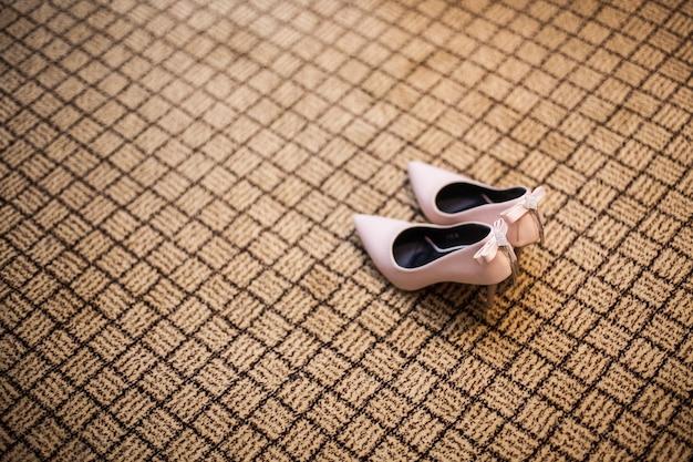 Sapatos de salto alto rosa no tapete no casamento