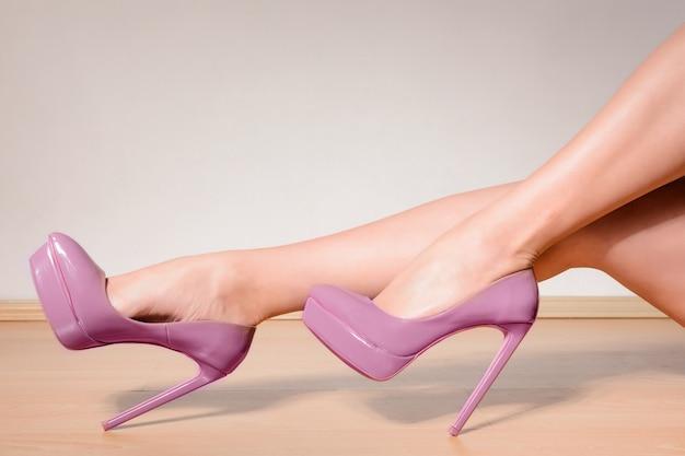 Sapatos de salto alto roxos em pernas femininas sexy