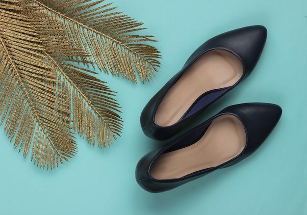 Sapatos de salto clássico com folhas de palmeira douradas sobre fundo azul pastel