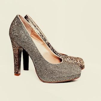 Sapatos de senhoras dourados em fundo branco.