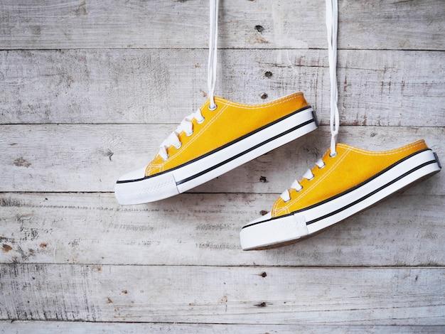 Sapatos de tênis amarelo com cadarço branco pendurado