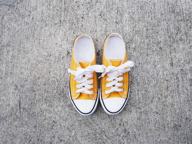 Sapatos de tênis amarelo na estrada de concreto