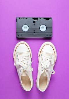 Sapatos de tênis branco retrô, fita de vídeo em um fundo roxo