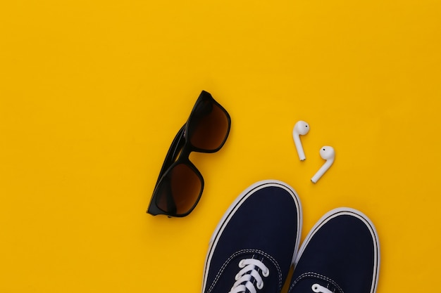 Sapatos de tênis e fones de ouvido sem fio, óculos de sol em fundo amarelo.