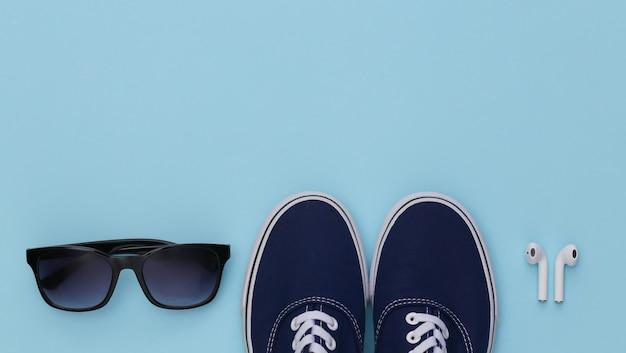 Sapatos de tênis e fones de ouvido sem fio, óculos de sol sobre fundo azul.
