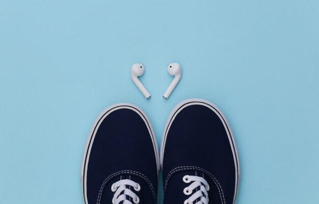 Sapatos de tênis e fones de ouvido sem fio sobre fundo azul.