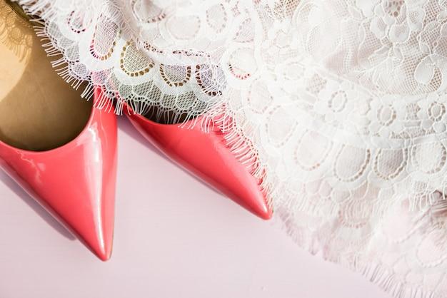 Sapatos de tribunal-de-rosa e vestido de renda em fundo rosa