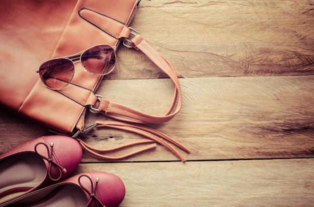 Sapatos e bolsas de couro para mulher colocada sobre um piso de madeira.