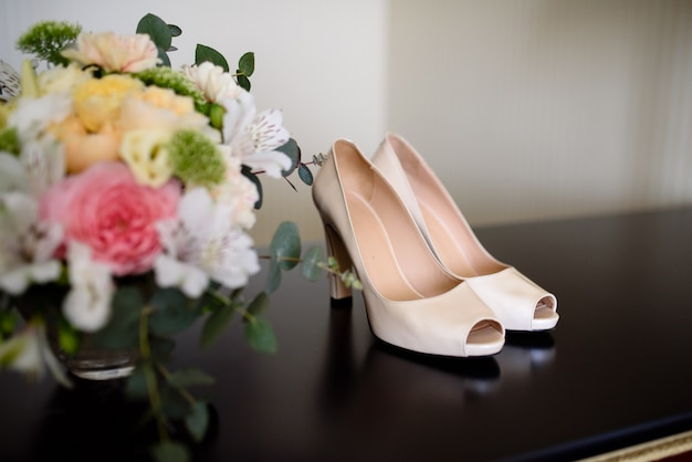 Sapatos e bouquet de noiva.