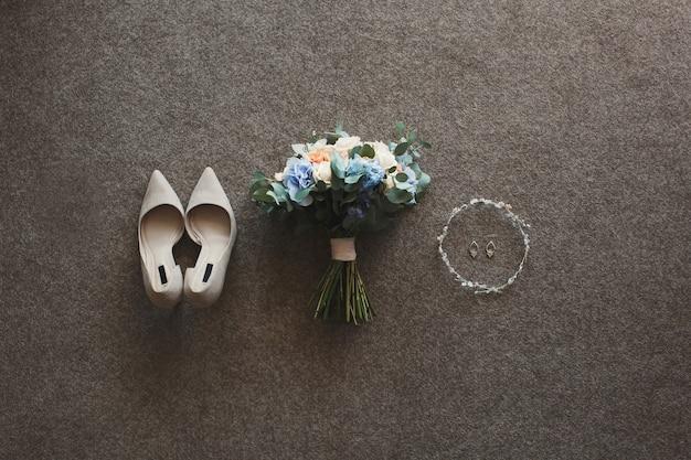 Sapatos e brincos de casamento bege e um buquê de casamento